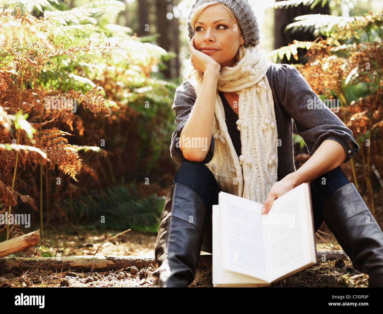 A woman in contemplation holding a book, outdoors - Stock Image