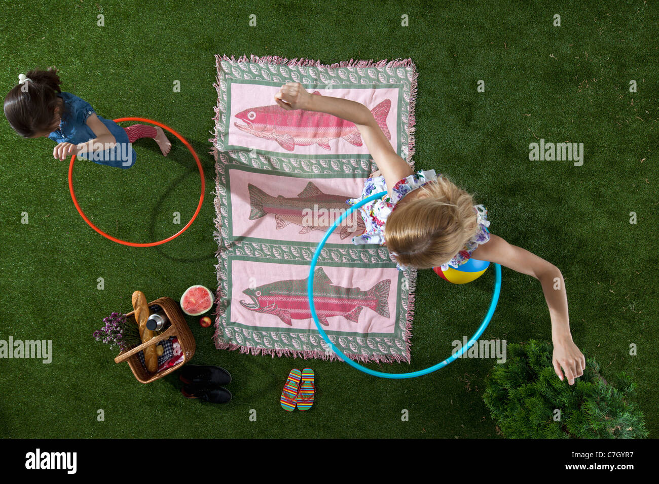 A mother and daughter using hula hoops at a picnic in the park, overhead view Stock Photo