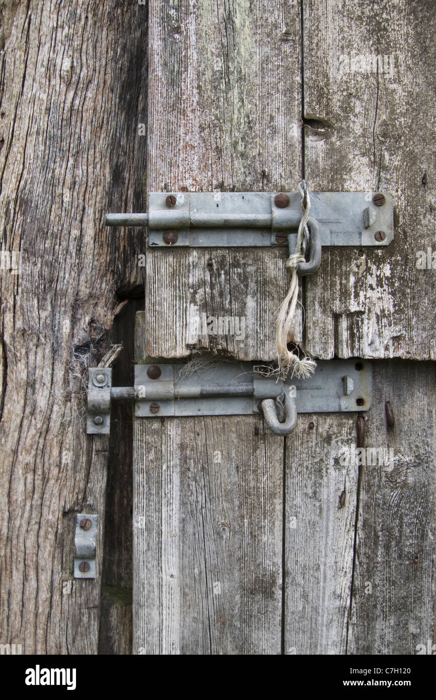 Two slide latches on a warped wooden door - Stock Image