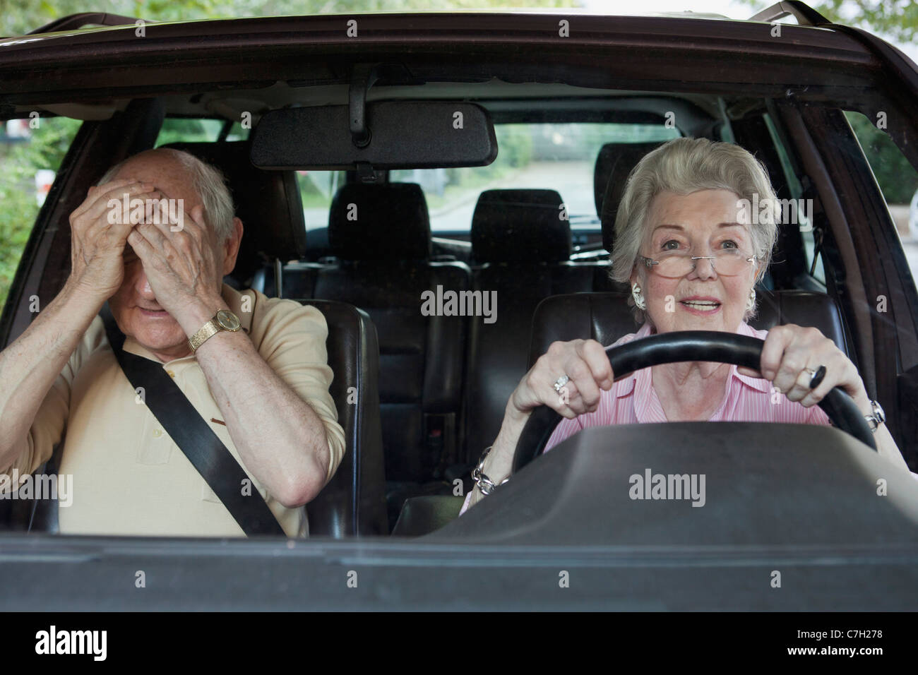 Woman has trouble driving while man in passenger seat despairs - Stock Image