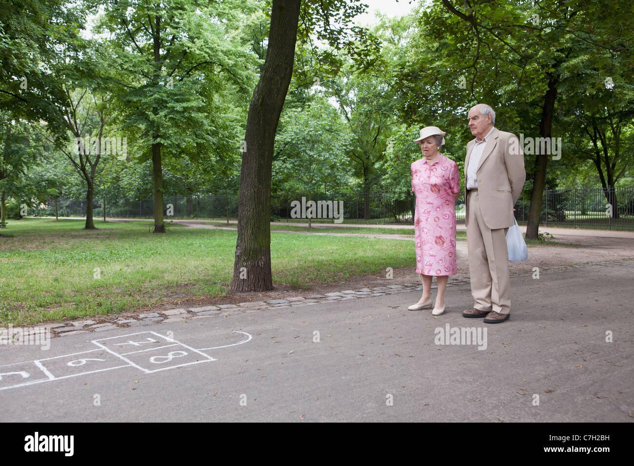 Senior couple contemplate hopscotch in the park - Stock Image