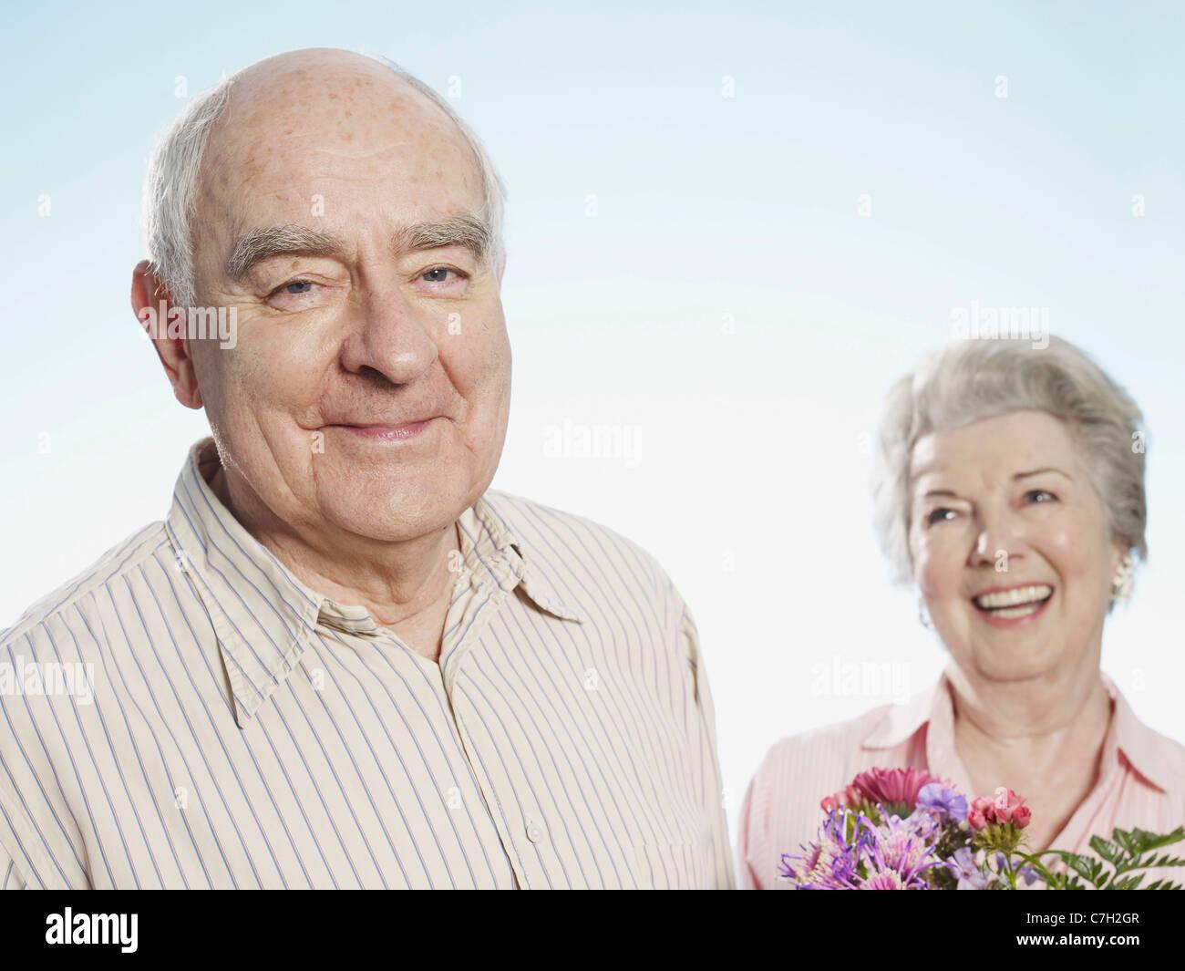 Senior man looks pleased that she likes the flowers Stock Photo