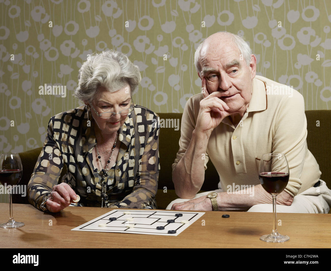 Senior couple play muehle and man looks impatient - Stock Image