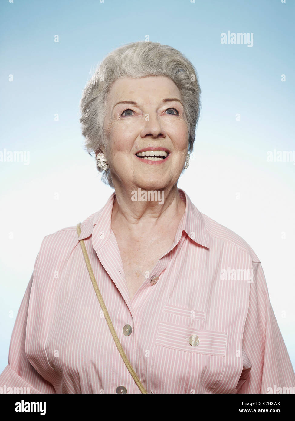 Profile of senior woman smiling and looking up - Stock Image