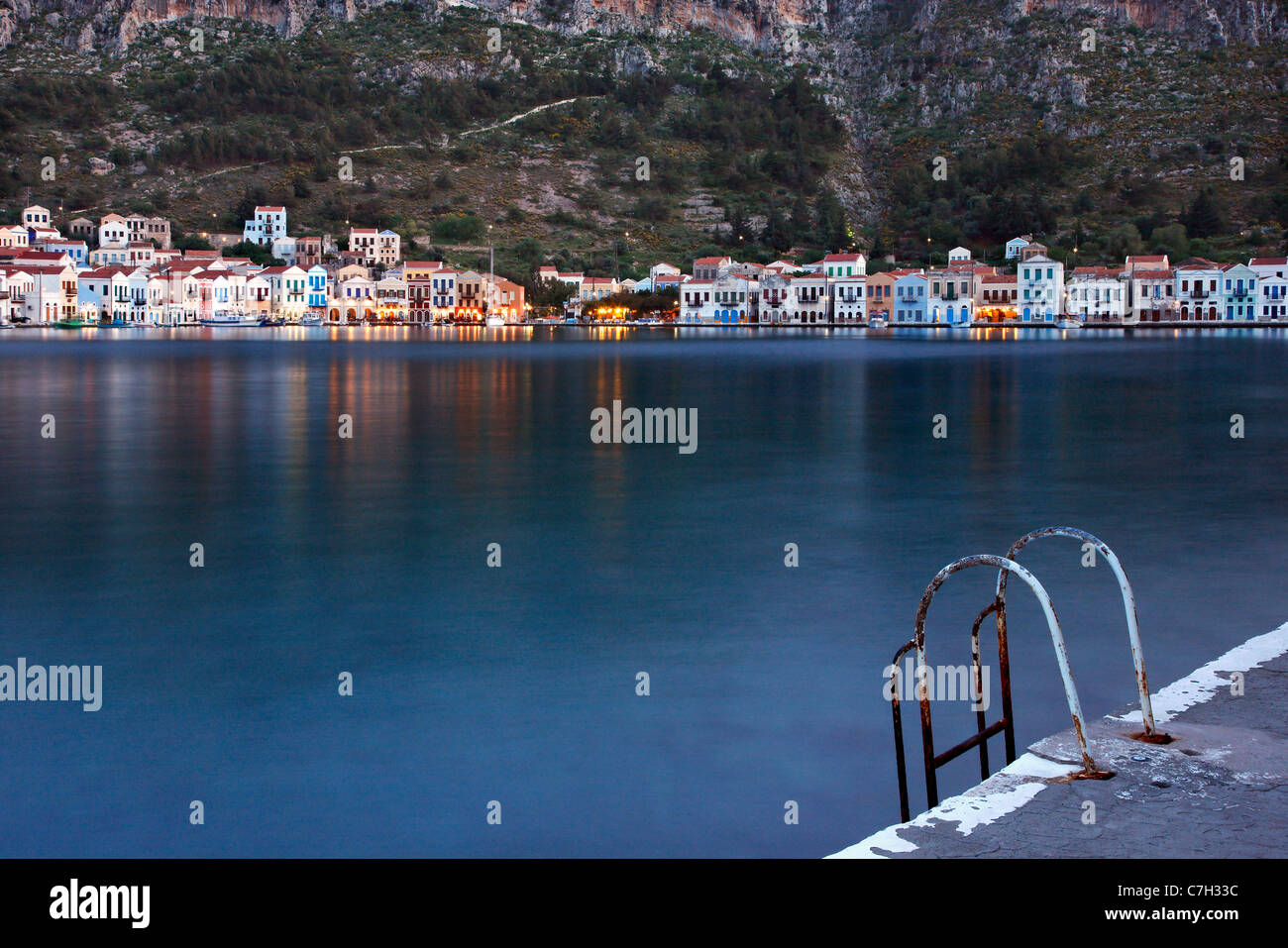 A ladder for swimmers in the picturesque harbor of Kastellorizo island, Dodecanese, Greece. (long exposure shot) - Stock Image