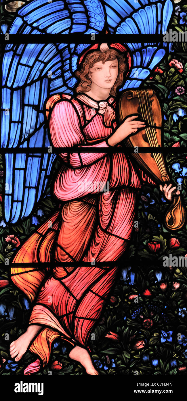 A stained glass window, by Edward Burne-Jones, depicting a winged angel playing a lute - Stock Image