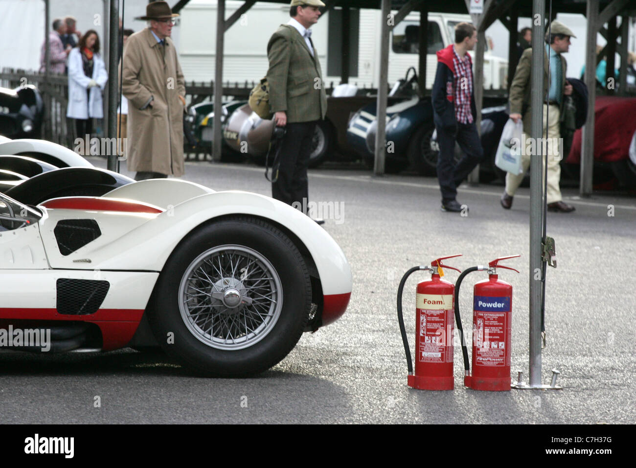 Fire extinguishers sitting next to the front of a historic racing car at the Goodwood Revival, West, Sussex, UK. - Stock Image