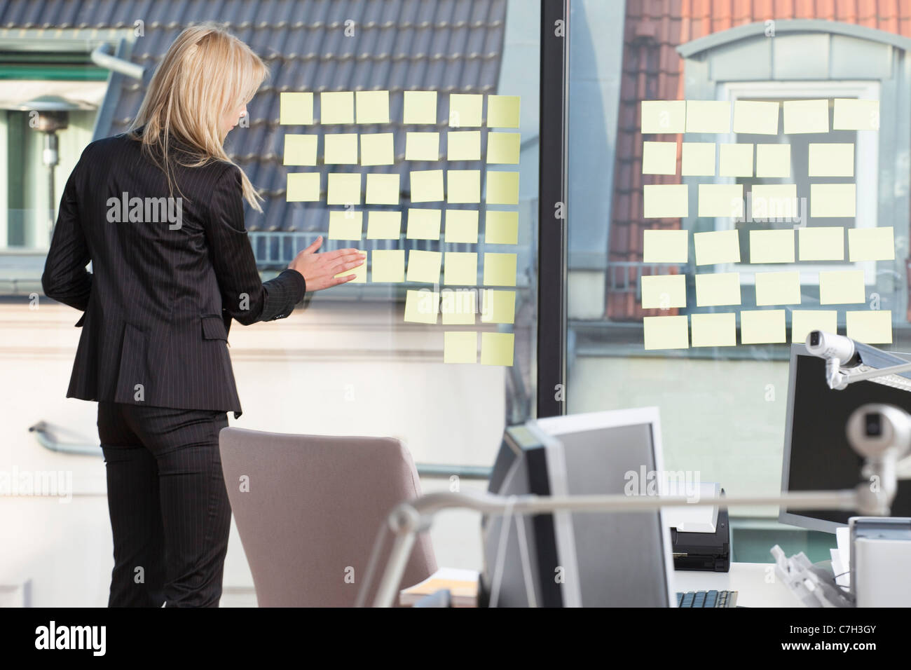 Businesswoman sticking many reminder notes to her office window - Stock Image