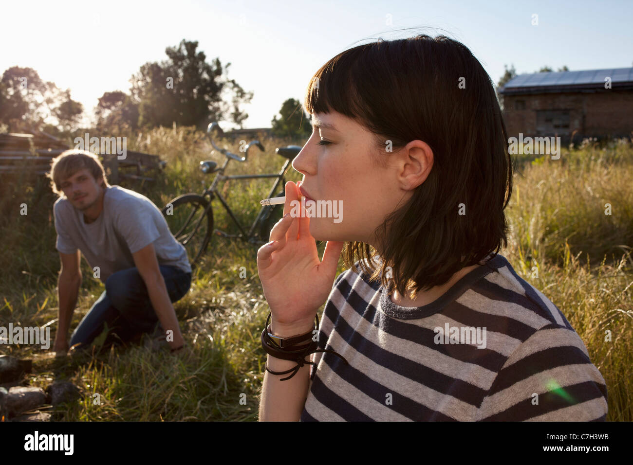 Girl smoking in field as guy in background watches - Stock Image