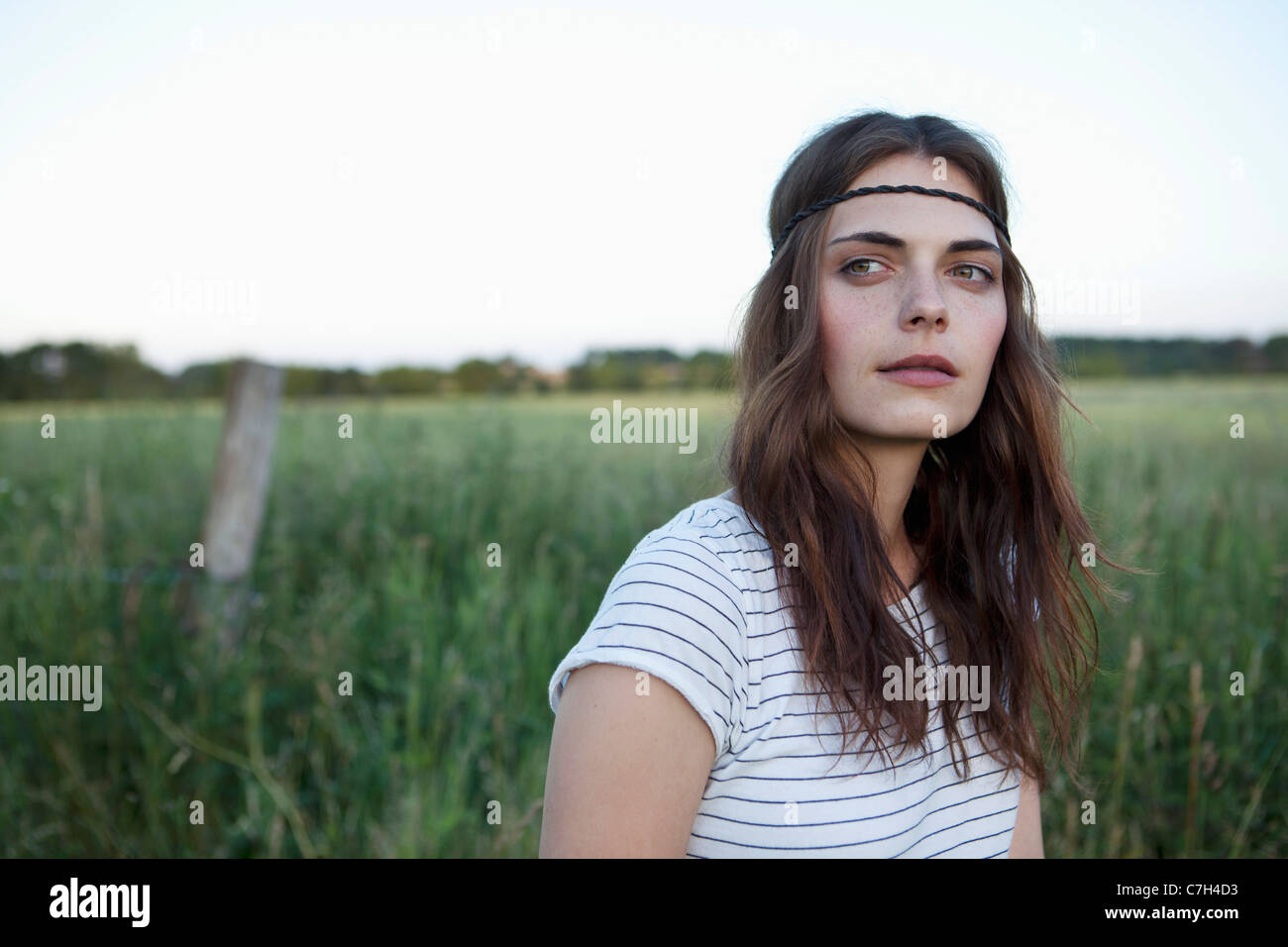 Profile of girl with hair band standing in field looking to the side - Stock Image