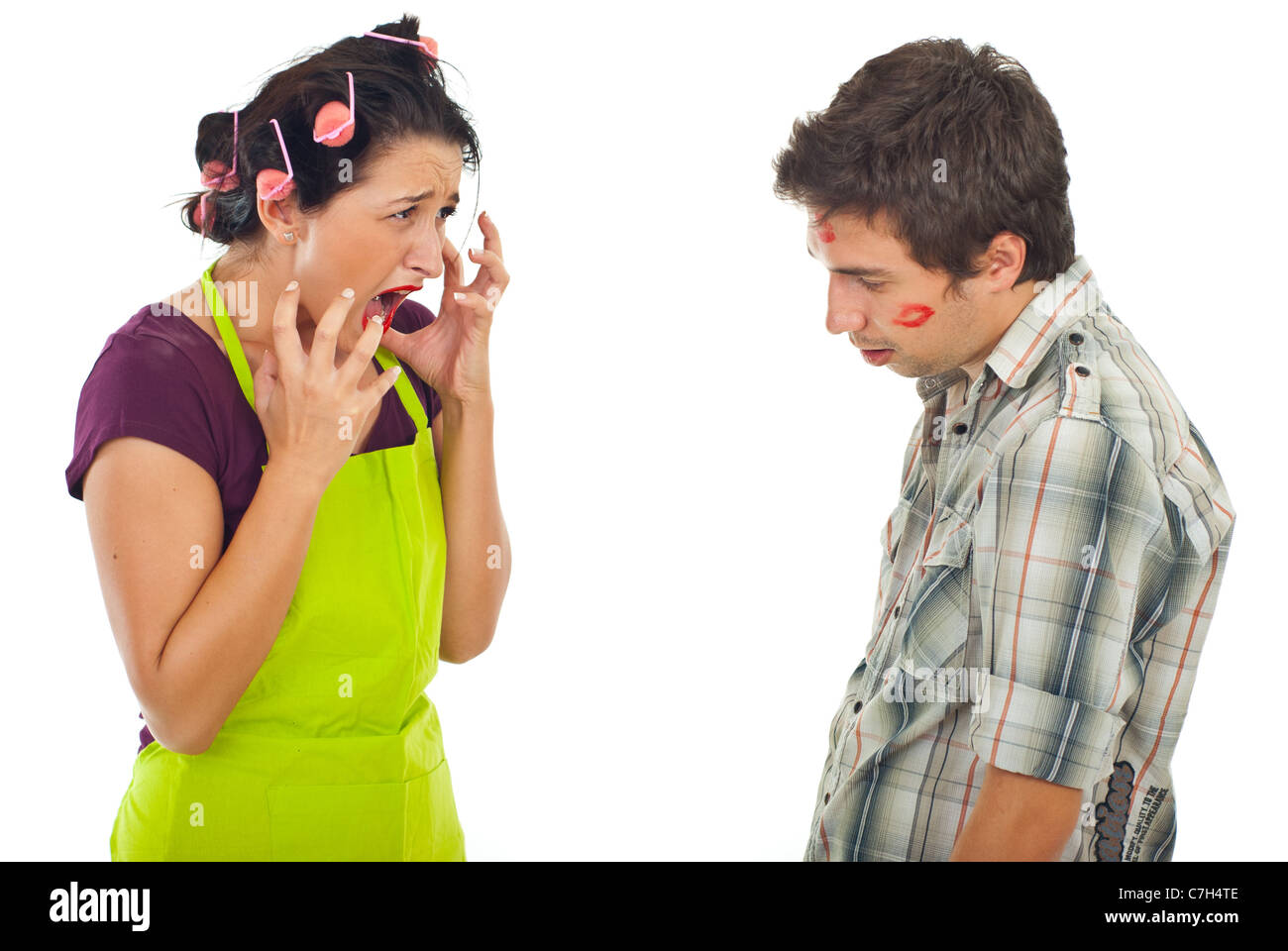 Angry housewife arguing with her unfaithful husband over white background - Stock Image