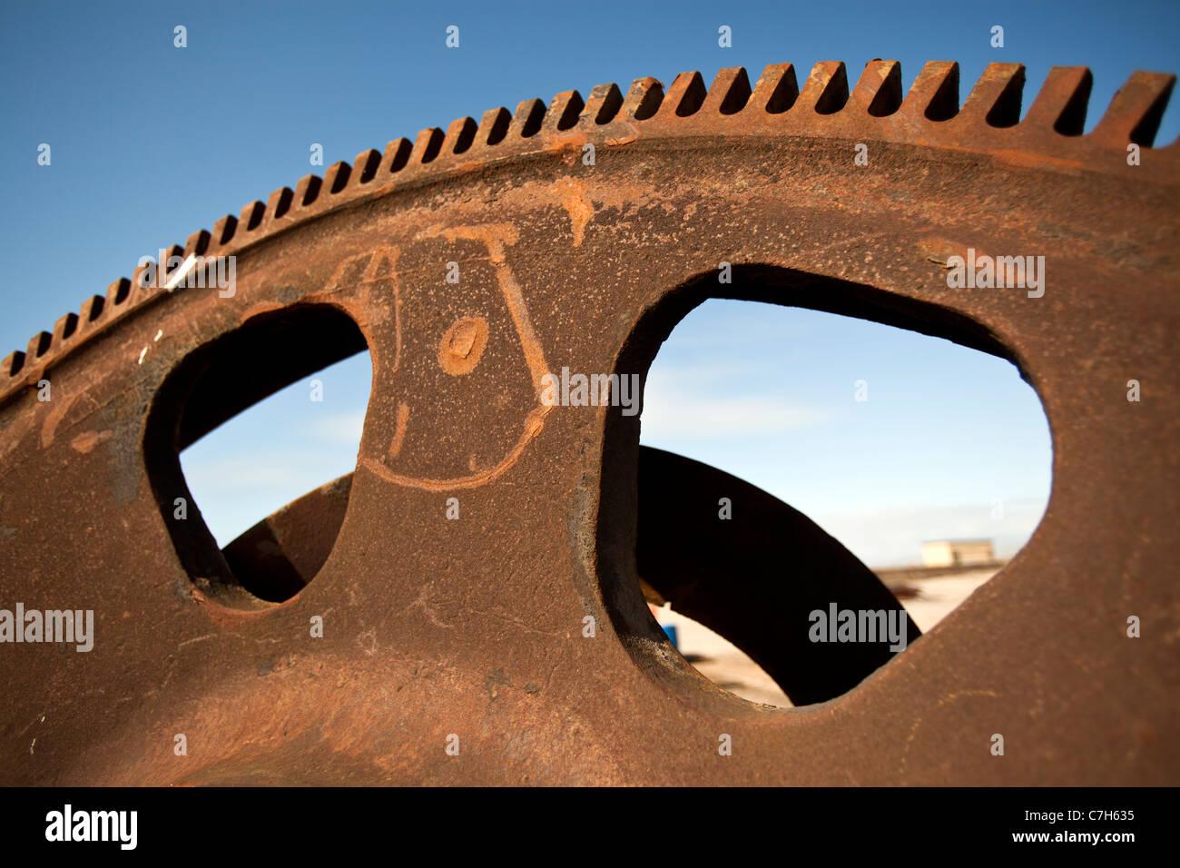 Teeth on a Rusty iron cog wheel against a blue sky. - Stock Image