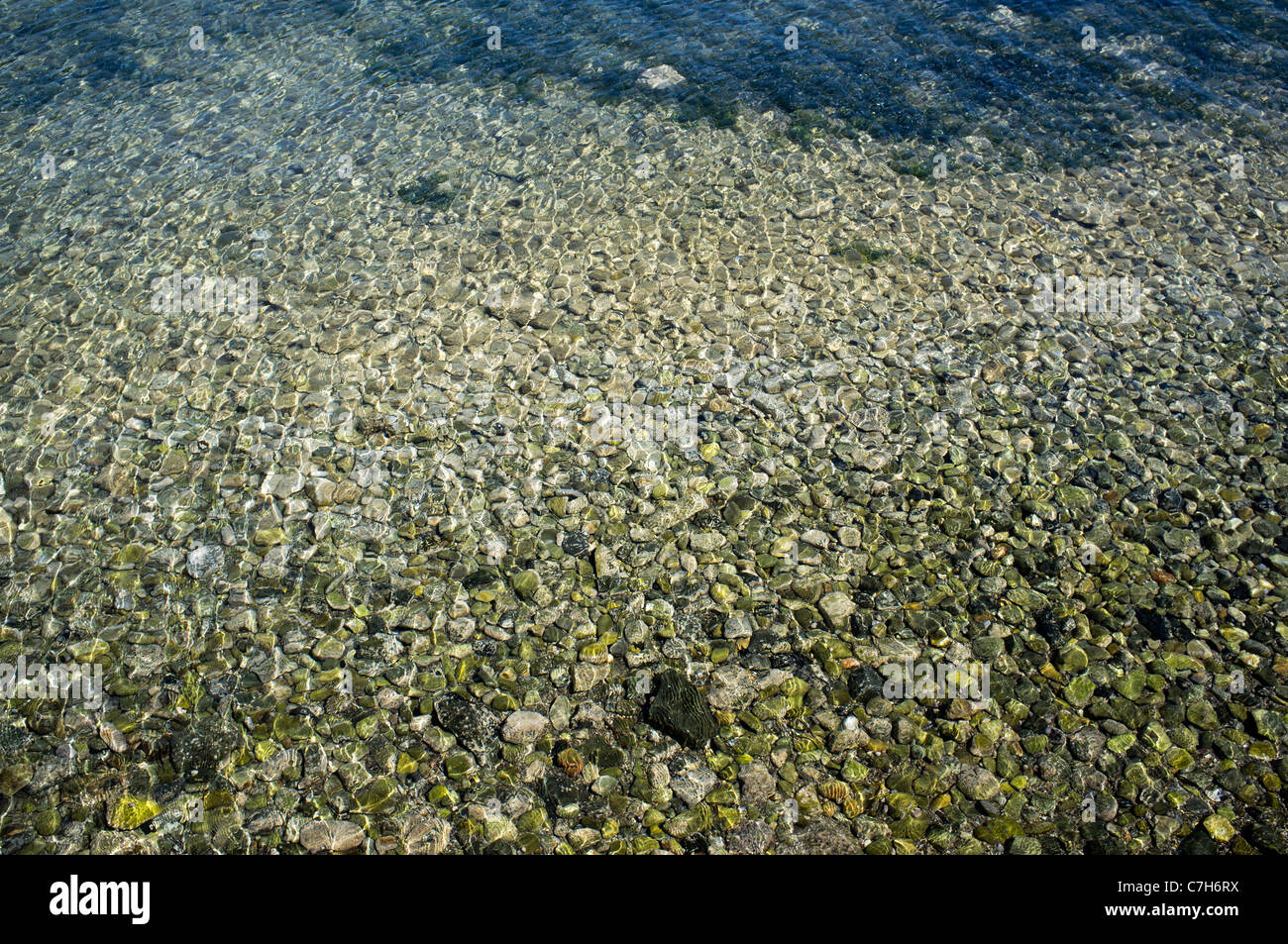Large pebbles under the water in the Bay of Mirabello on the  Greek island of Crete - Stock Image