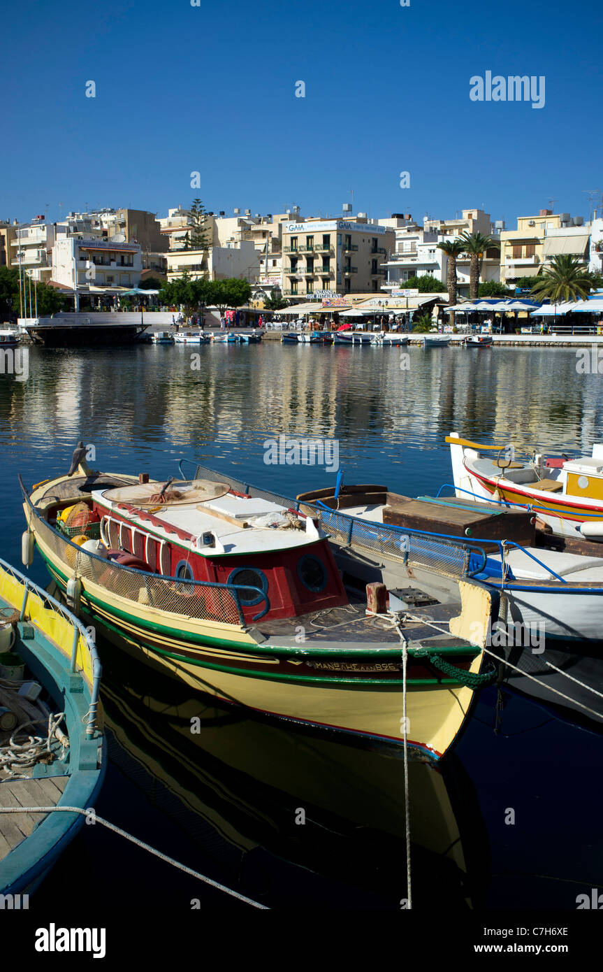 Traditional colourful fishing boats line the Lake Voulimeni in Agios Nikolaos on the Greek island of Crete - Stock Image