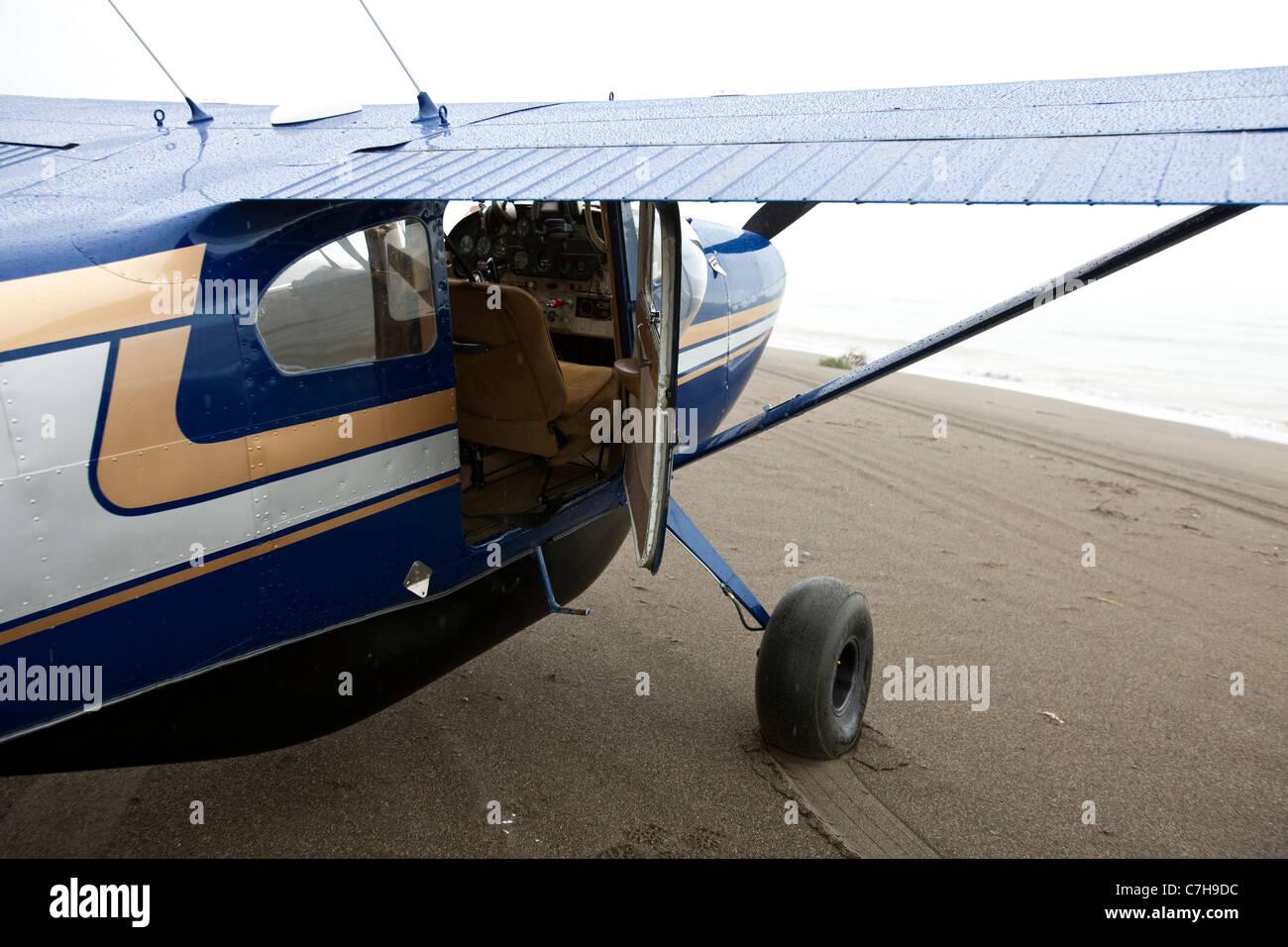 Prop plane parked on a sandy beach, Lake Clark National Park near Silver Salmon Creek Lodge, Alaska, United States - Stock Image