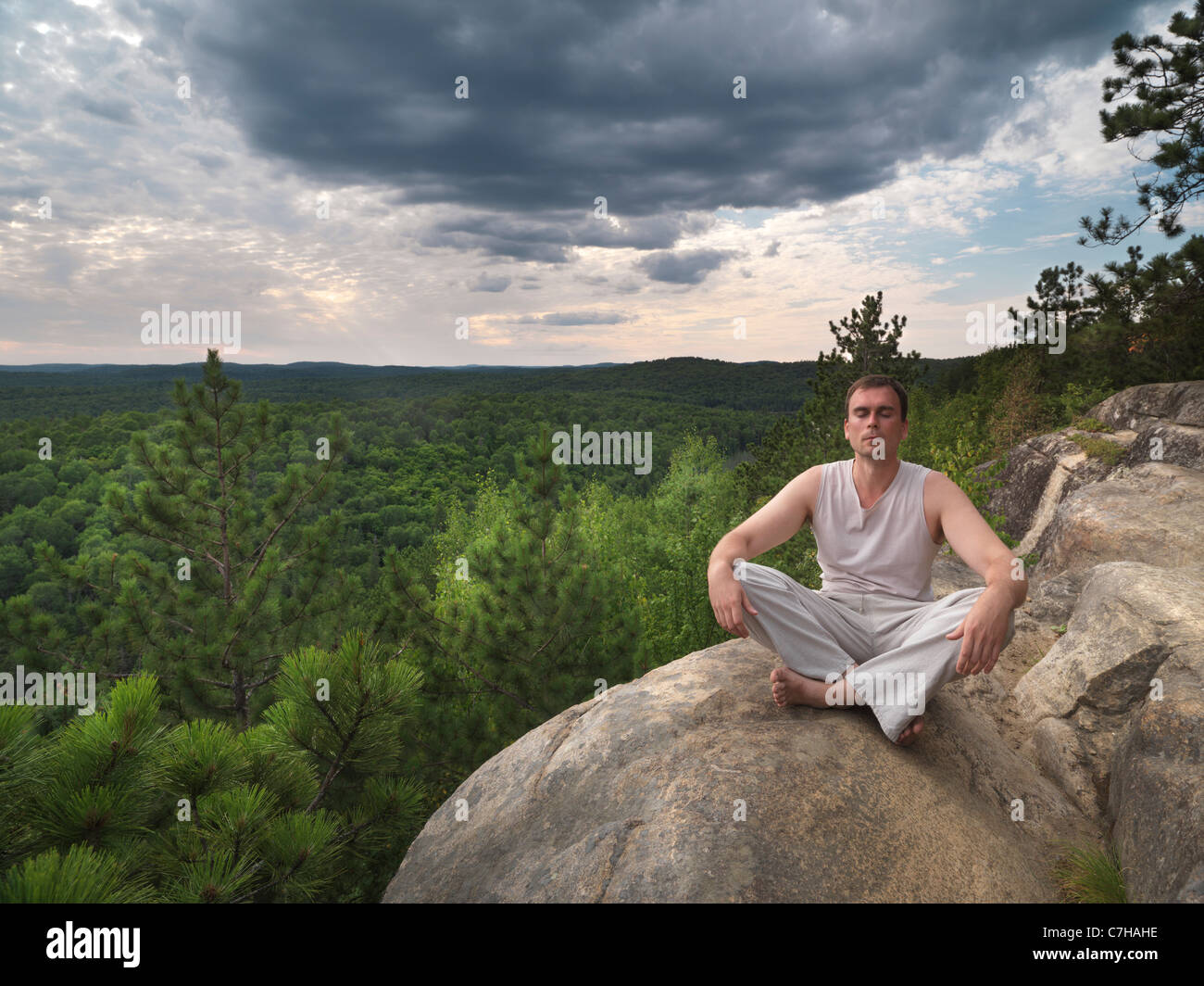 Young man meditating in the nature. Algonquin, Ontario, Canada. - Stock Image