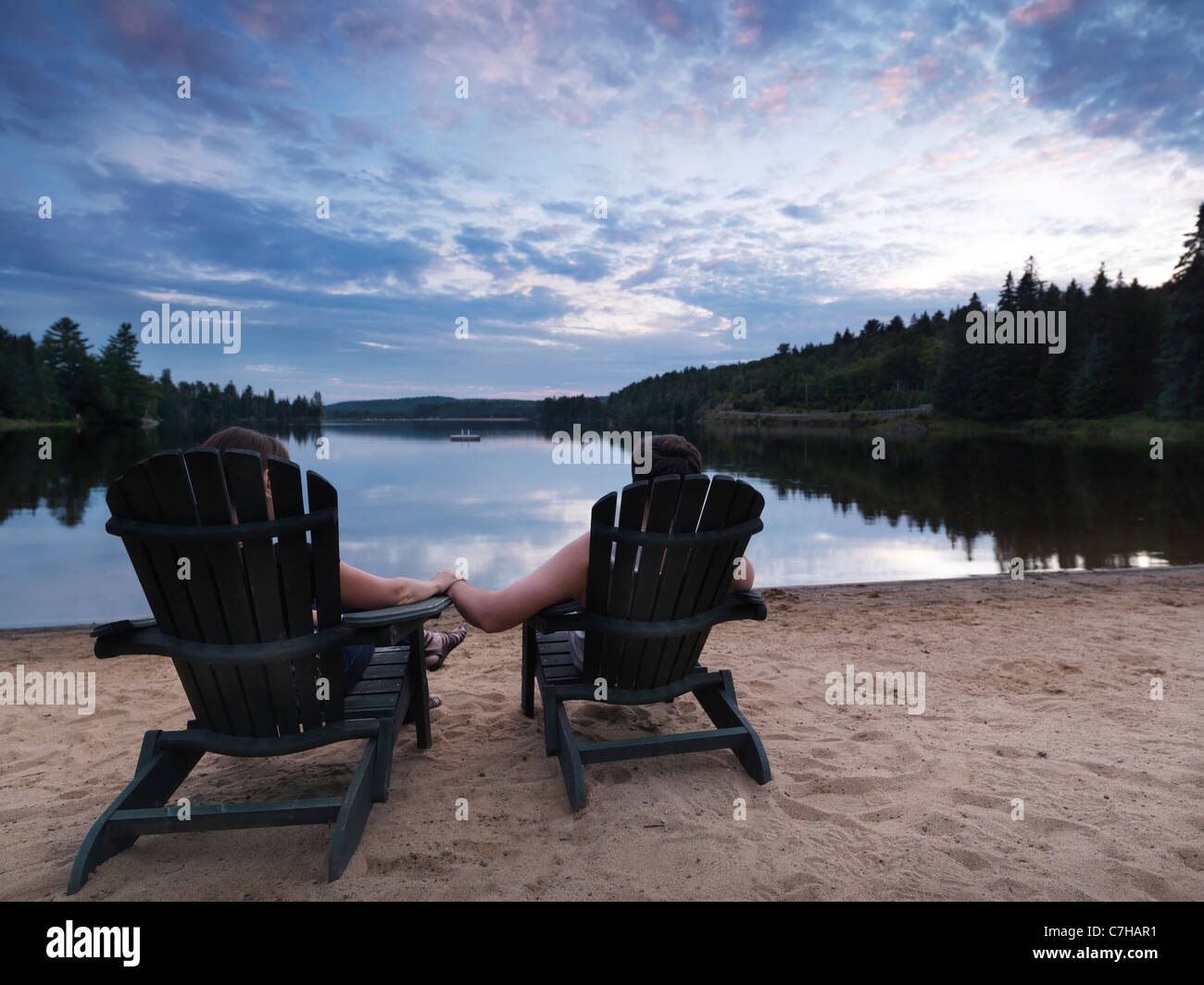 Couple enjoying sunset at the Lake of Two Rivers in Algonquin Provincial Park, Ontario, Canada. - Stock Image