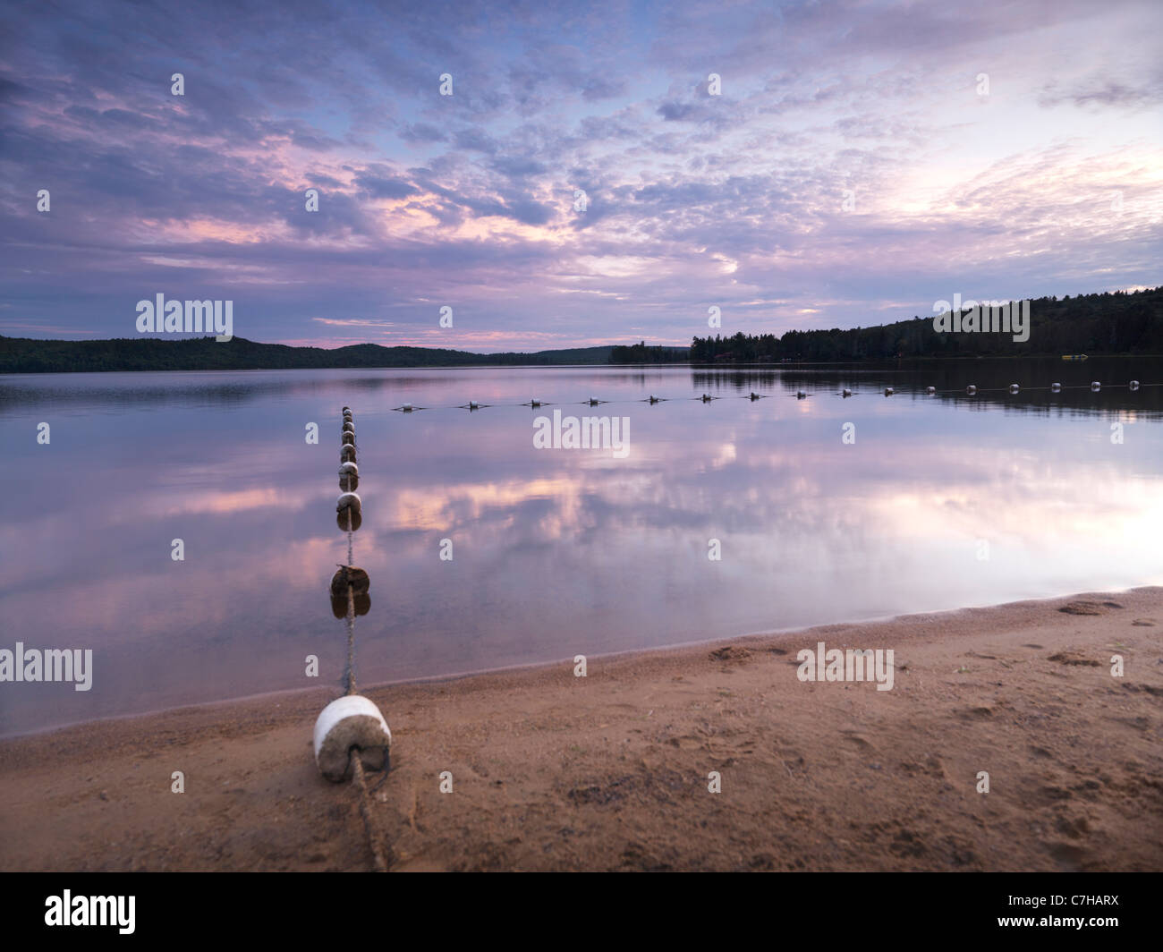 Swimming zone buoy line. Algonquin Provincial Park summertime nature scenery of the Lake of Two Rivers at sunset. - Stock Image