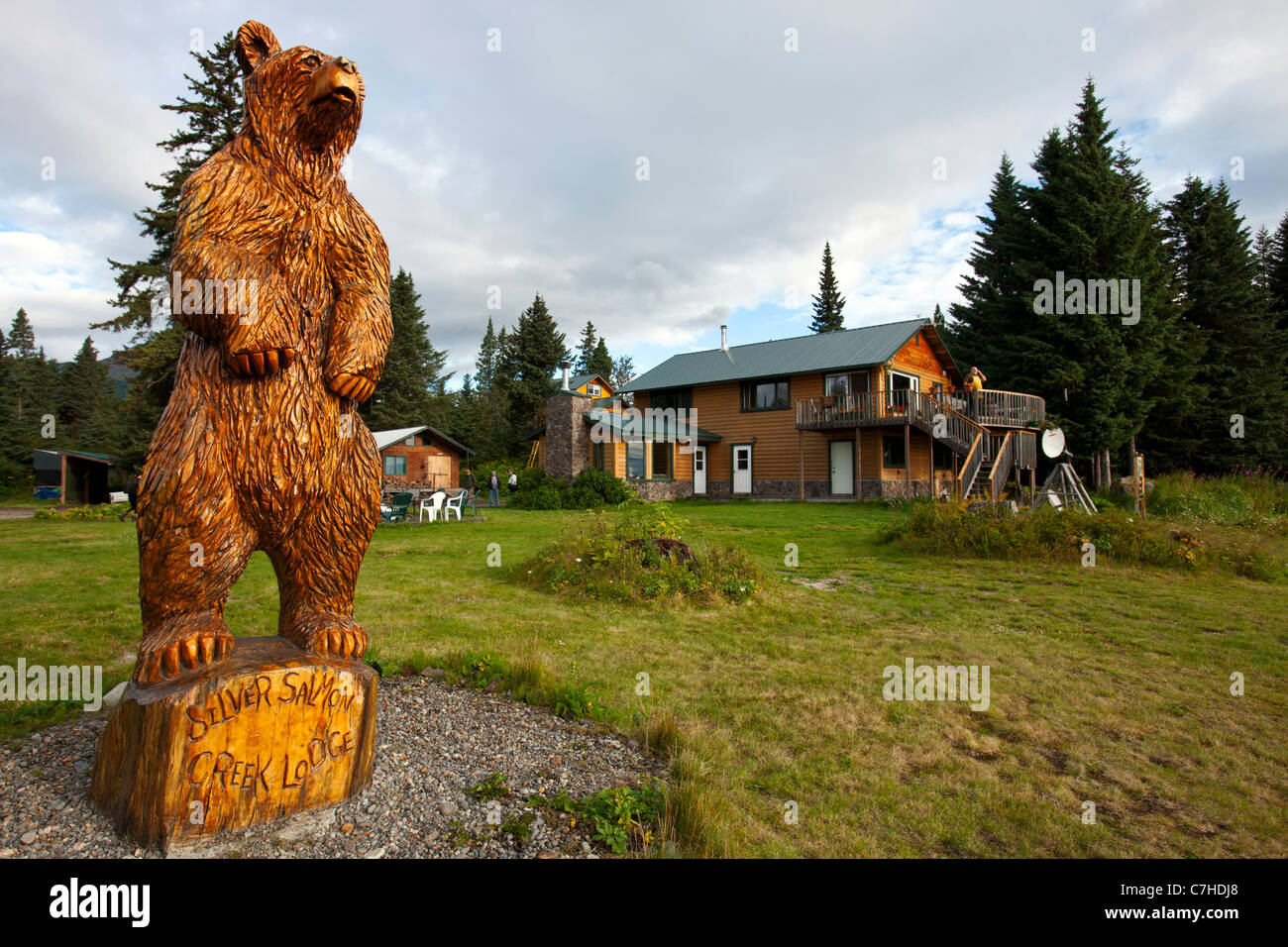 View of Silver Salmon Creek Lodge with wooden grizzly bear statue, Lake Clark National Park, Alaska, United States - Stock Image
