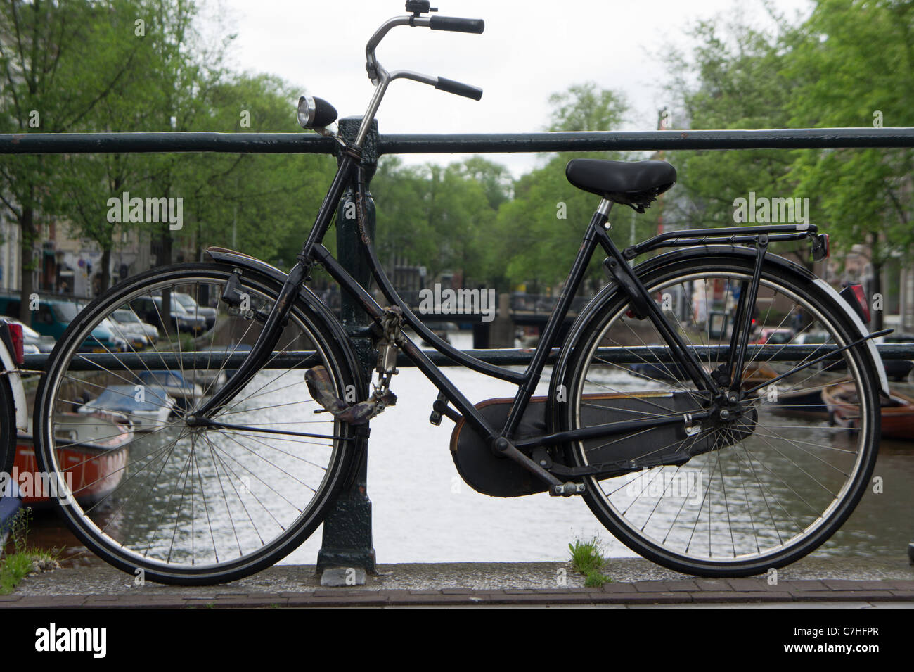 Old bicycle chained to bridge over a canal in Amsterdam, Holland Stock Photo