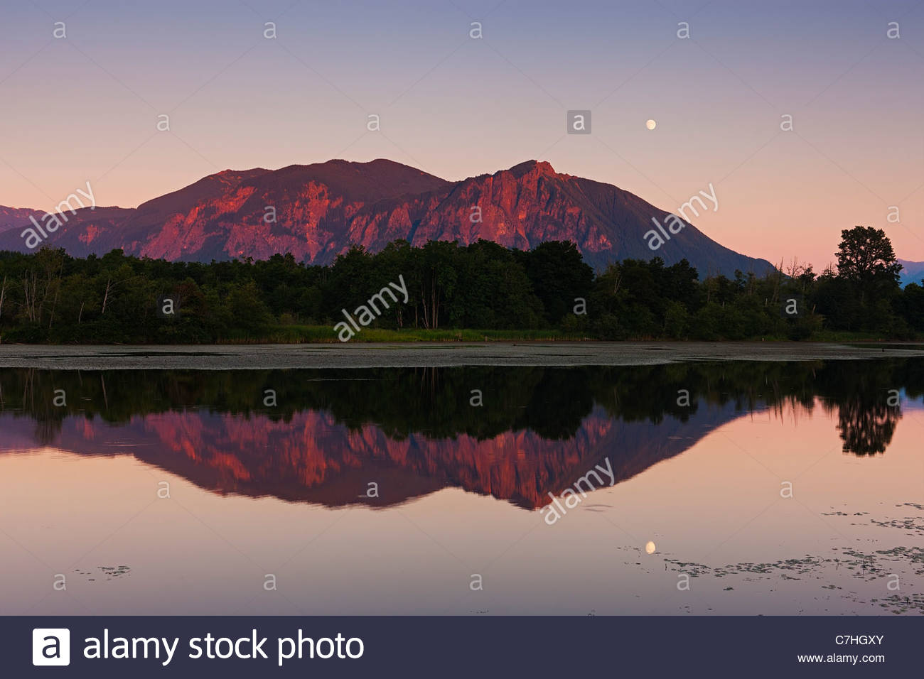 The nearly full moon rises over Mount Si, a 4,167 foot (1,270 meter) mountain located near North Bend, Washington. - Stock Image