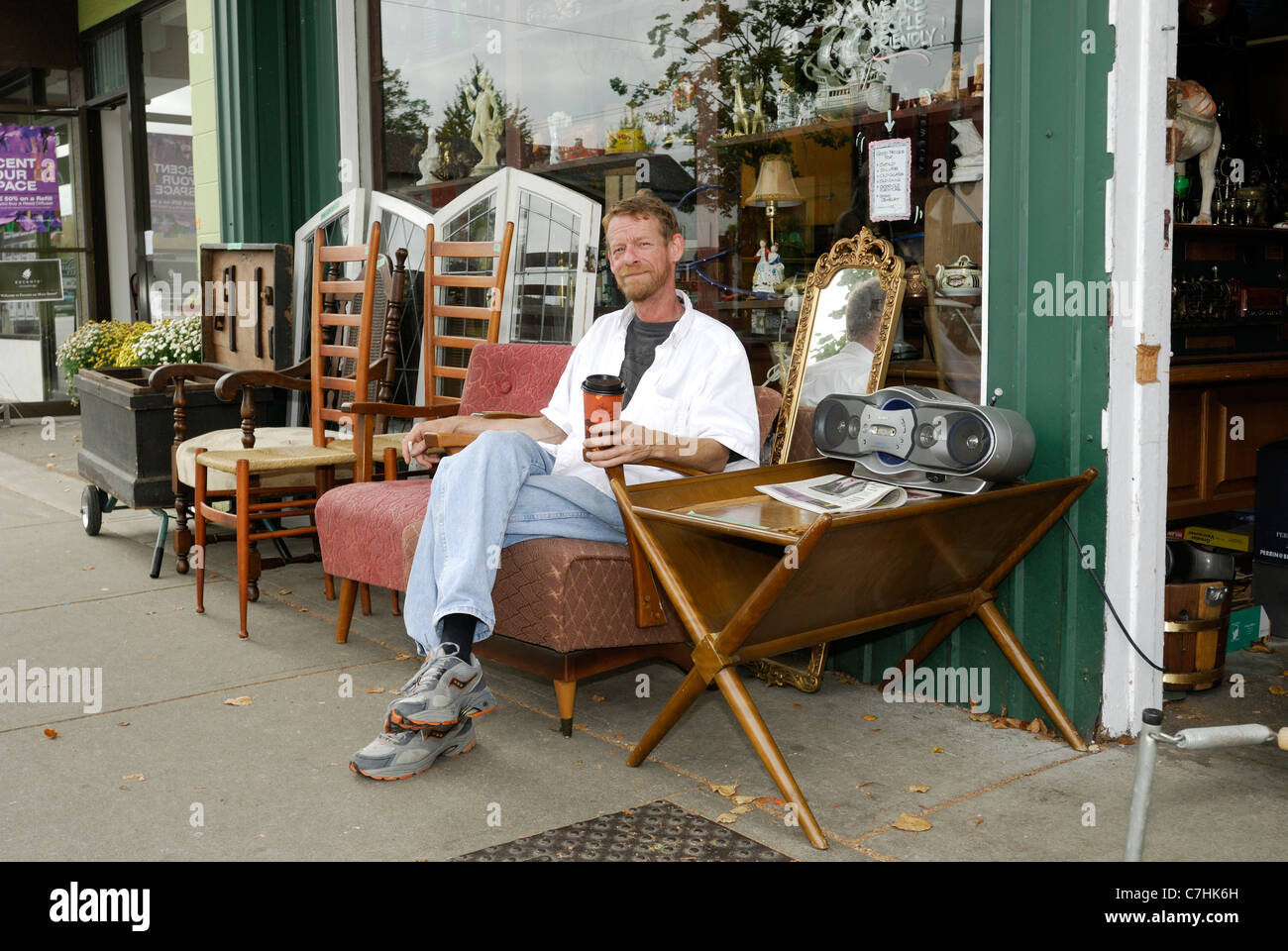 Used furniture shopkeeper sitting outside on a piece of furniture.Used and antique furniture stores located on Main - Stock Image