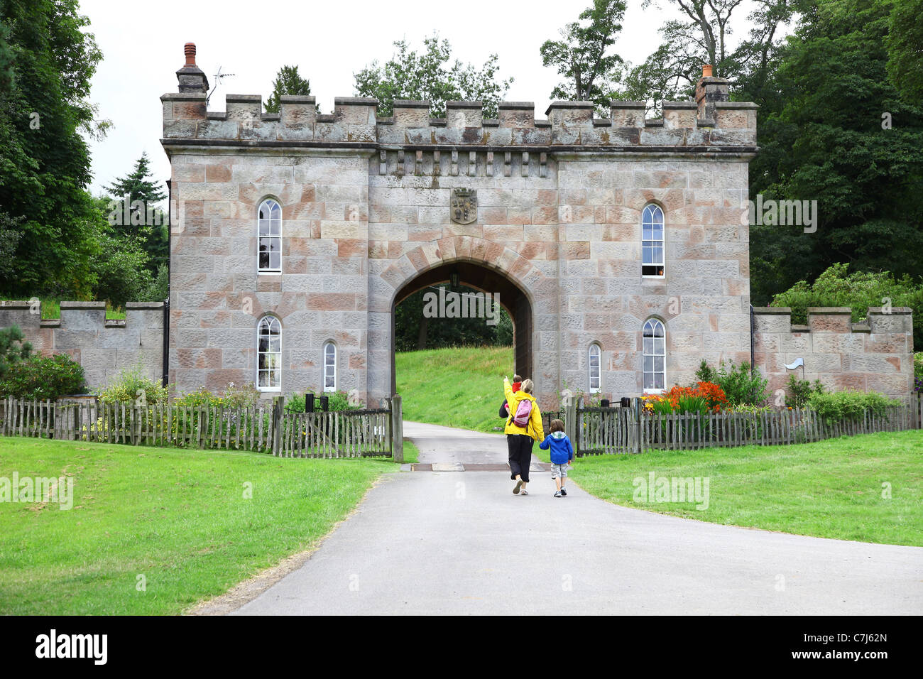 A mother and father with their two children walking by the gate house or gatehouse  at Cholmondeley Castle Cheshire, Stock Photo