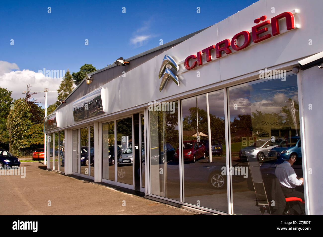 reflections on the front windows of ian fleming citroen car showroomreflections on the front windows of ian fleming citroen car showroom on a sunny day in urban dundee,uk