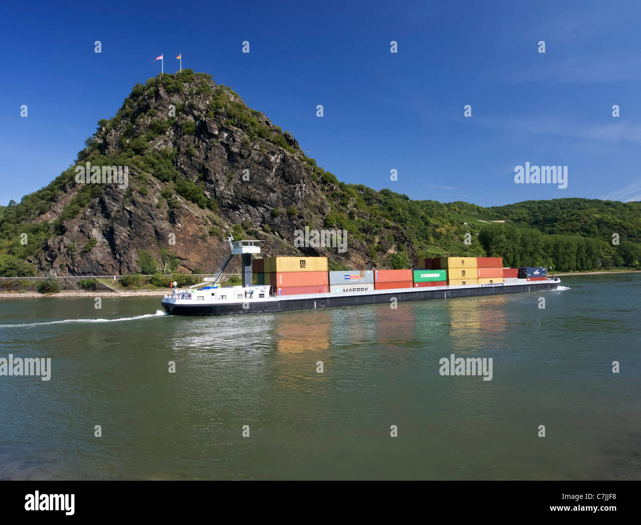 Large barge carrying container freight passes Loreley rock on River Rhine in Germany - Stock Image
