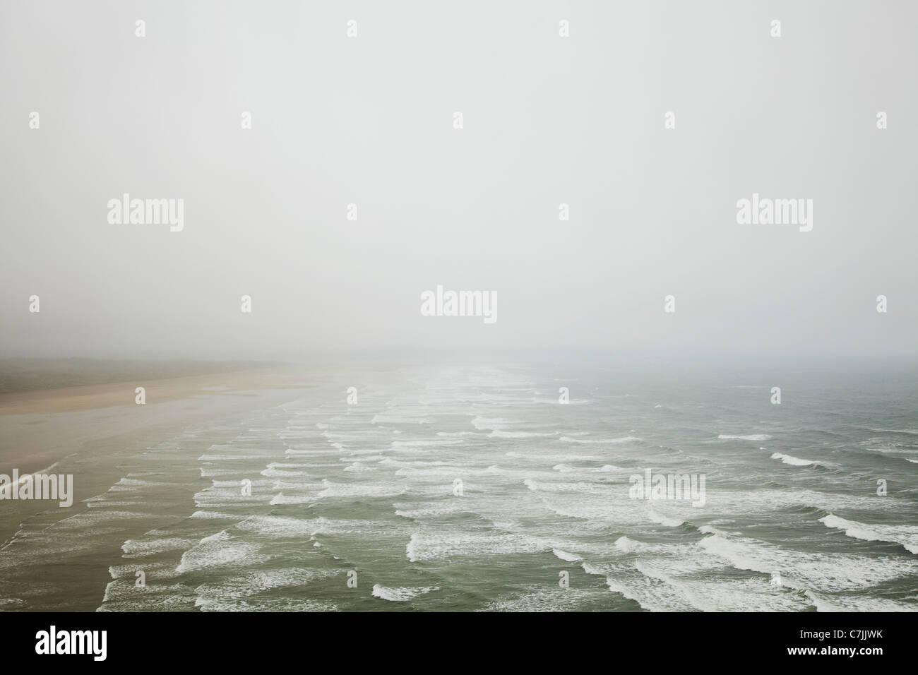 Waves crashing on foggy beach - Stock Image