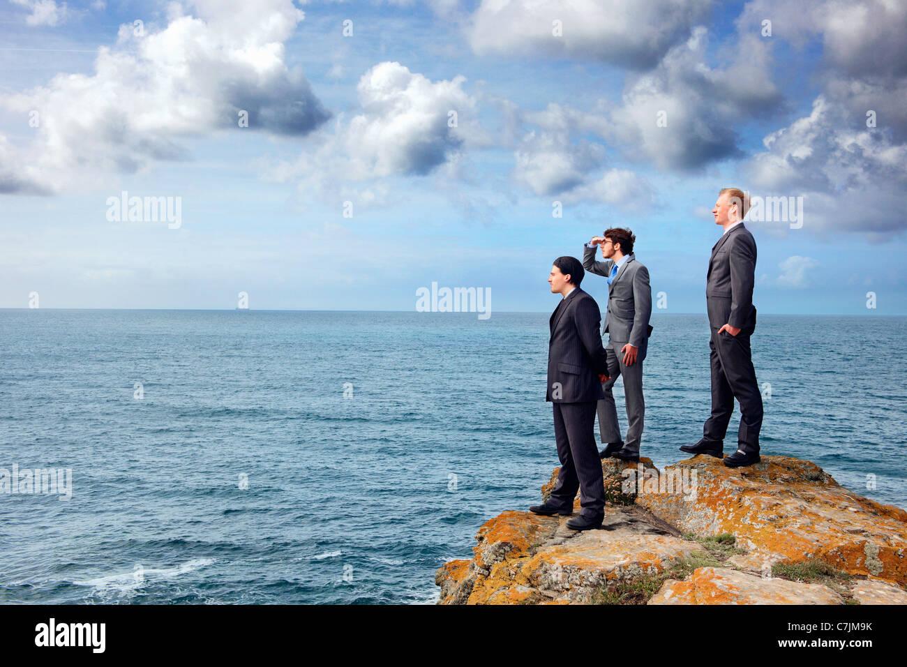 Businessmen standing on cliff edge - Stock Image