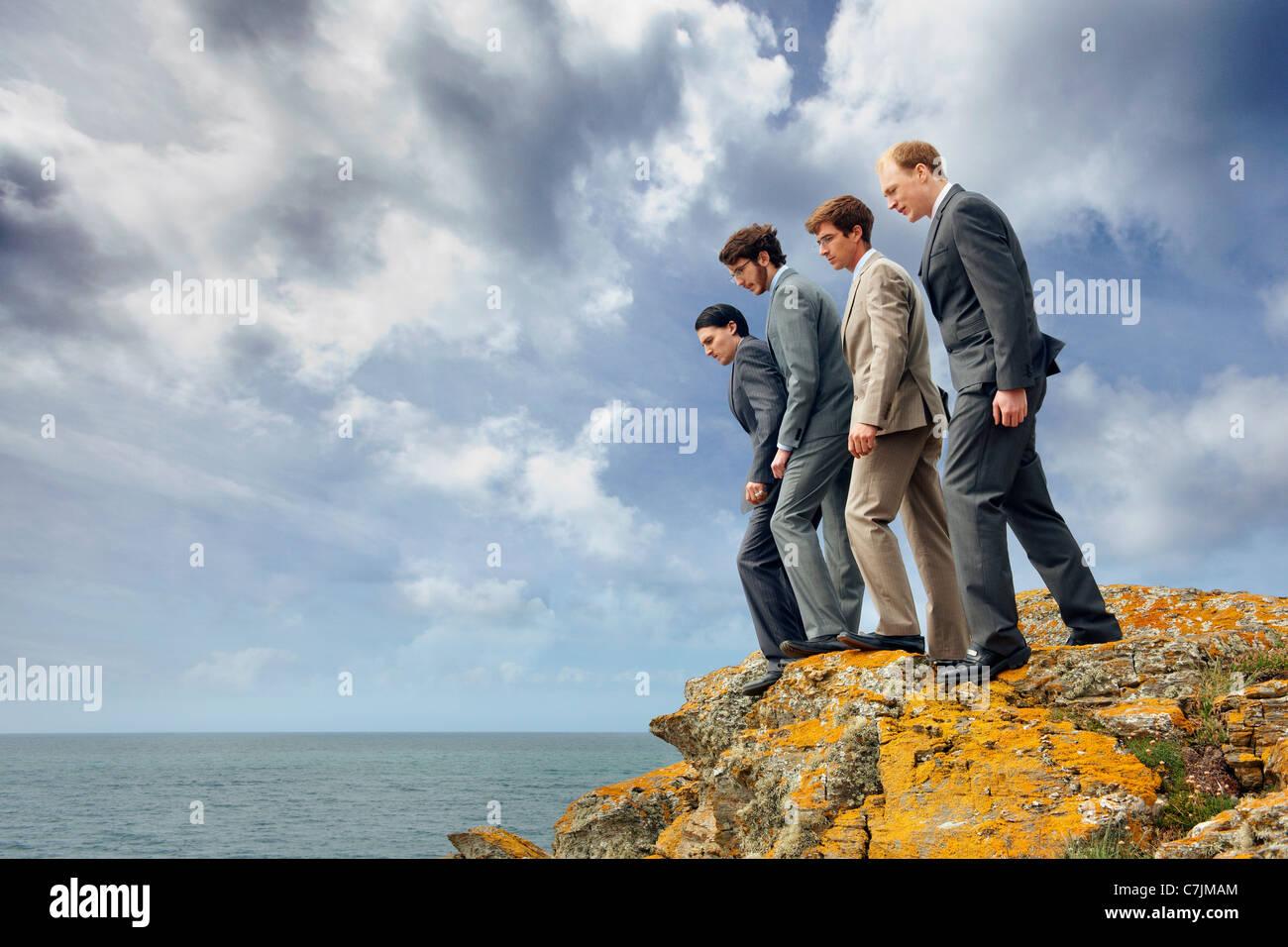Businessmen peering over cliff edge - Stock Image