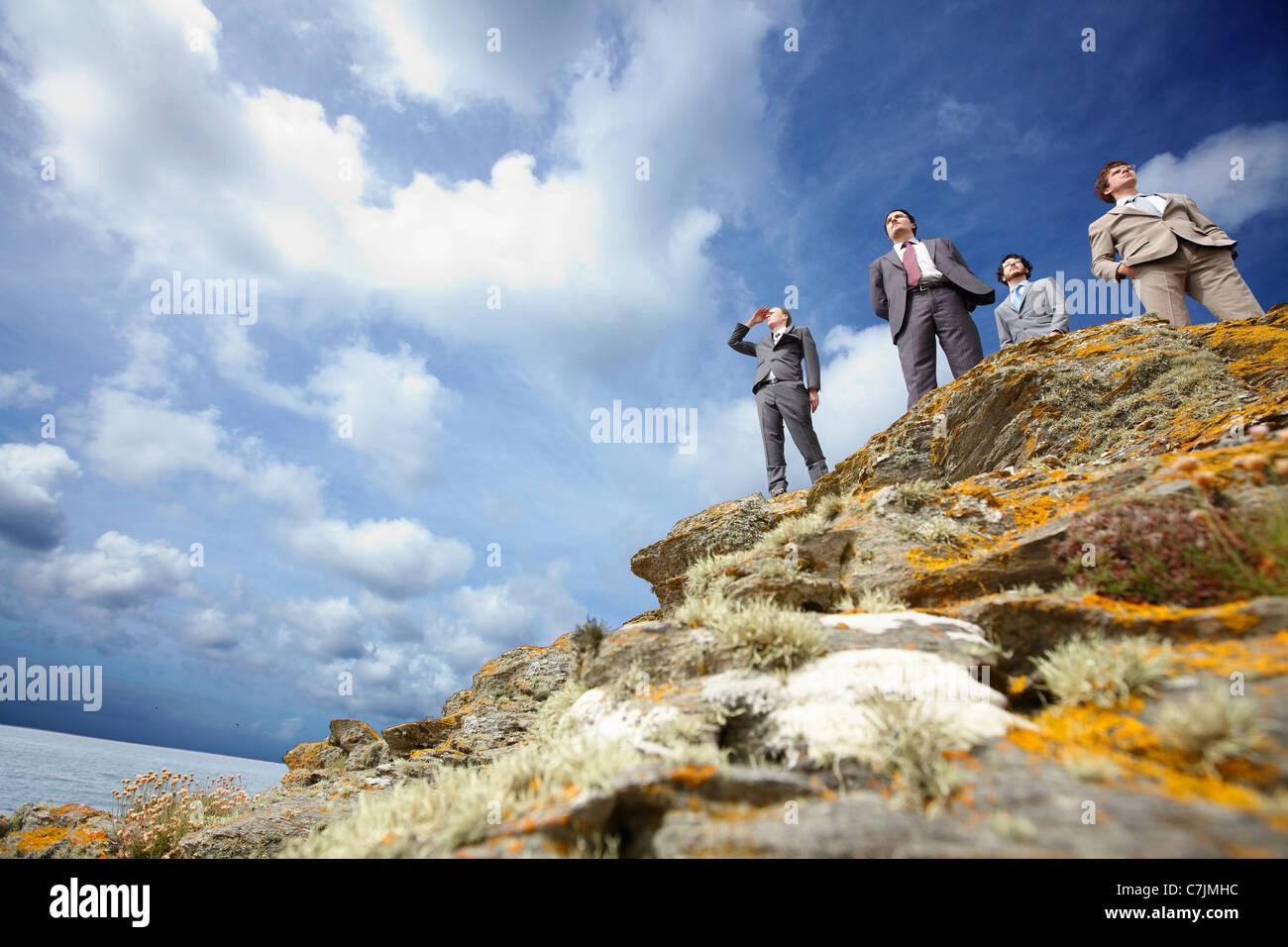 Businessmen standing on cliff edge Stock Photo
