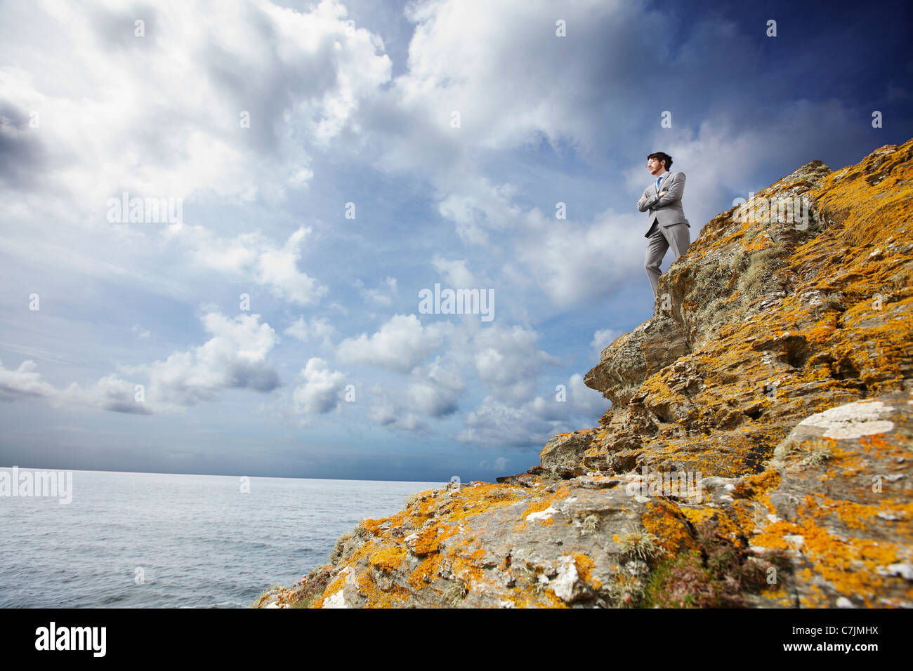 Businessman standing on cliff edge - Stock Image