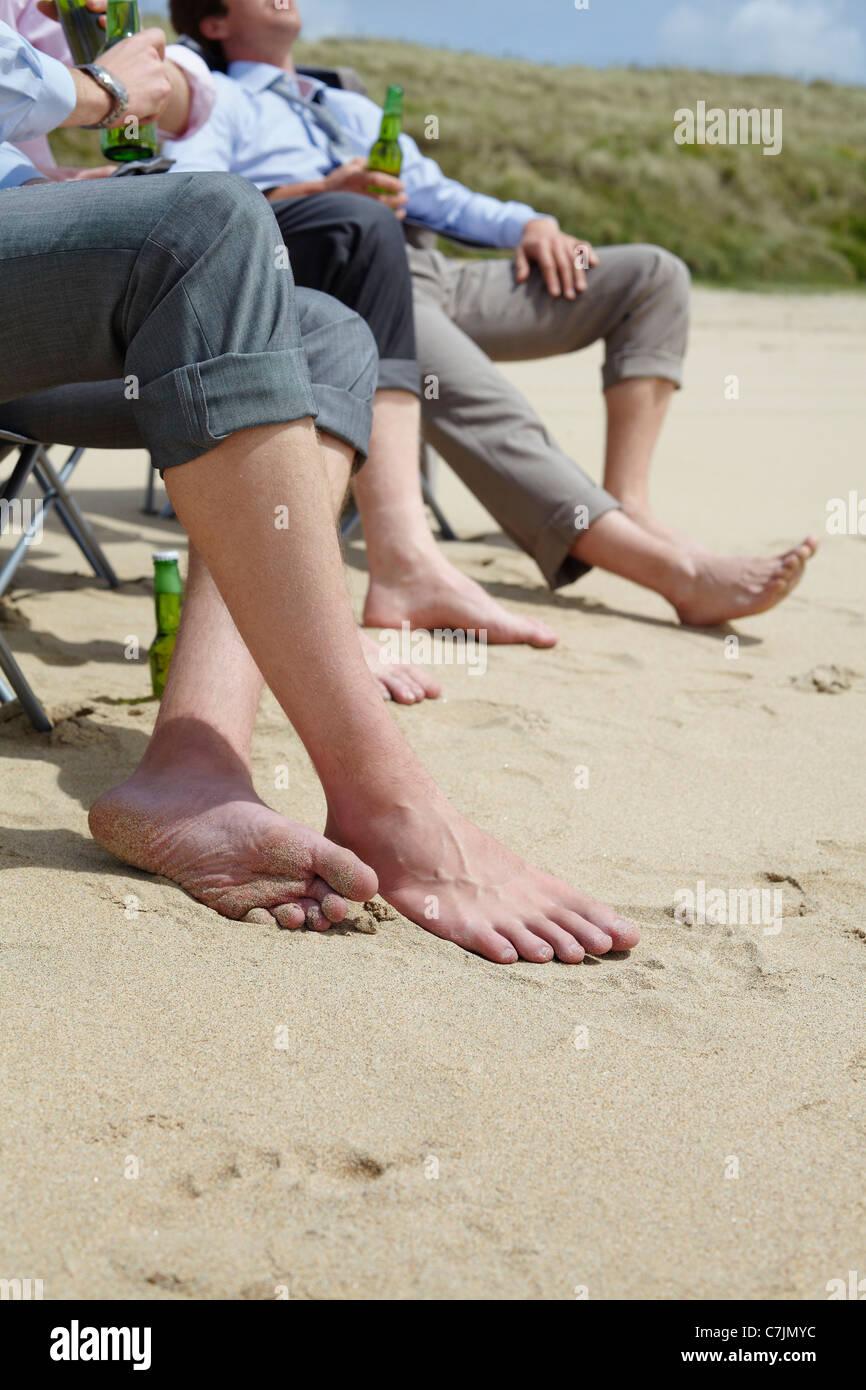 Businessmen's bare feet on beach Stock Photo