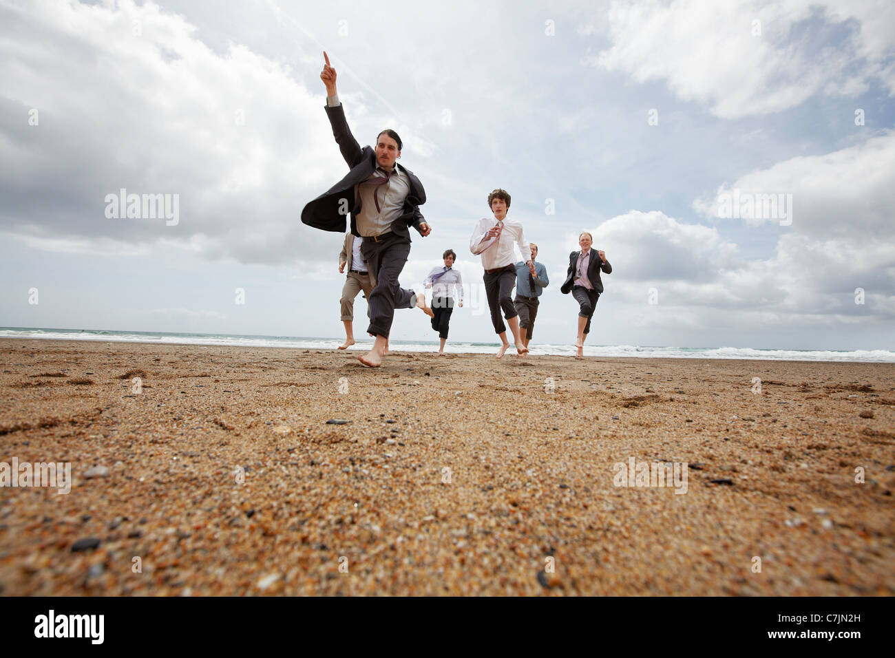 Businessmen running on beach Stock Photo