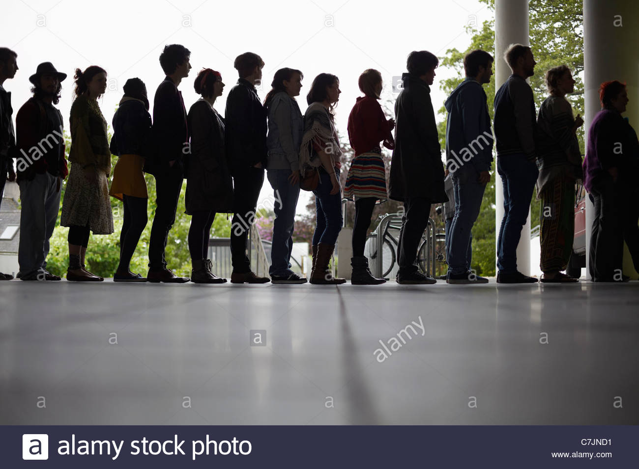 Silhouette of people standing in line - Stock Image