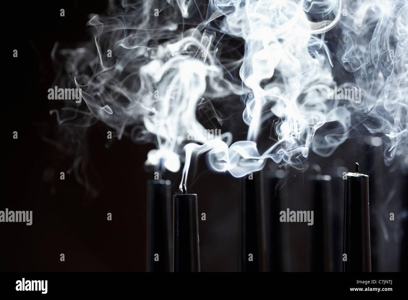 Close up of smoking black candles - Stock Image