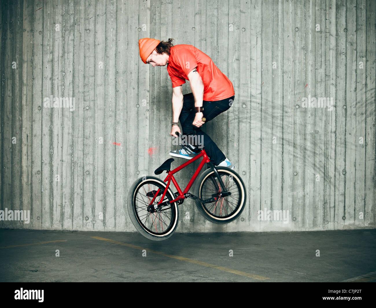 Man doing tricks on bmx bike indoors - Stock Image