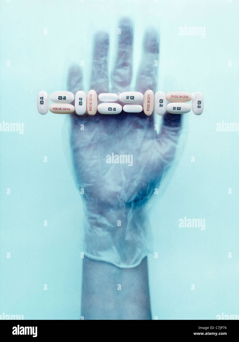 Gloved hand holding pills - Stock Image