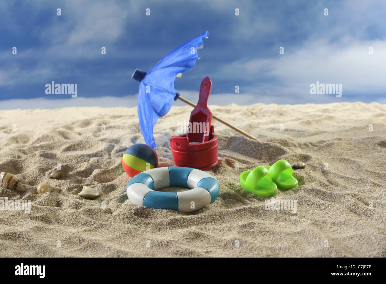 Sun Umbrella with toys, water polo and swimming ring at the beach Stock Photo