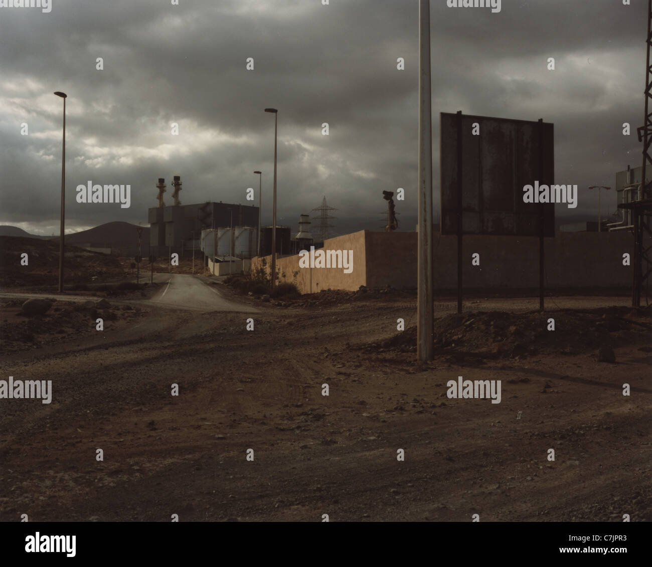 Industrial buildings on dirt road - Stock Image