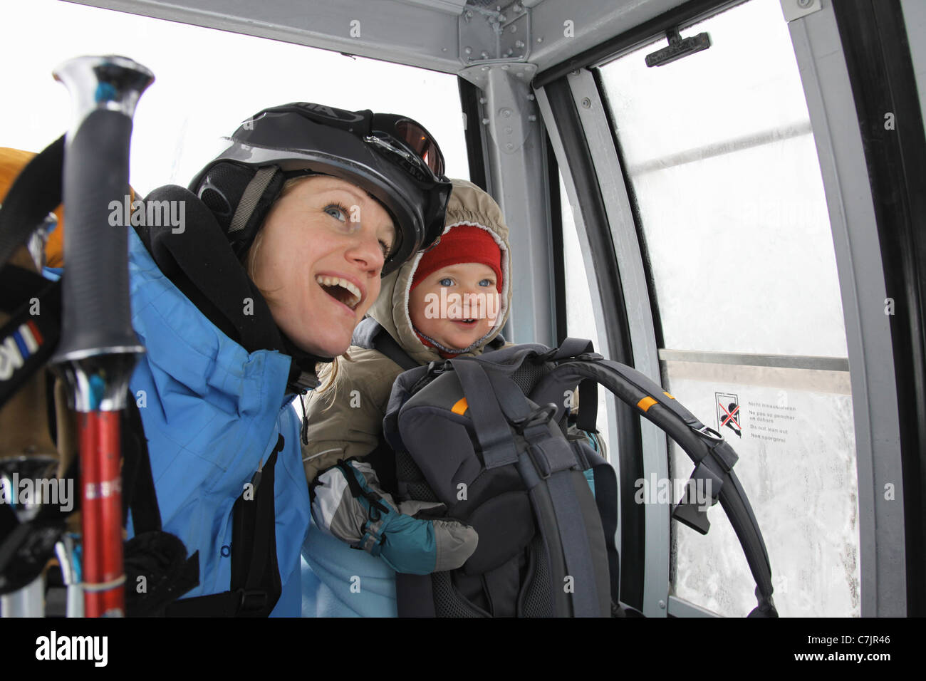 Mother and child riding ski lift - Stock Image