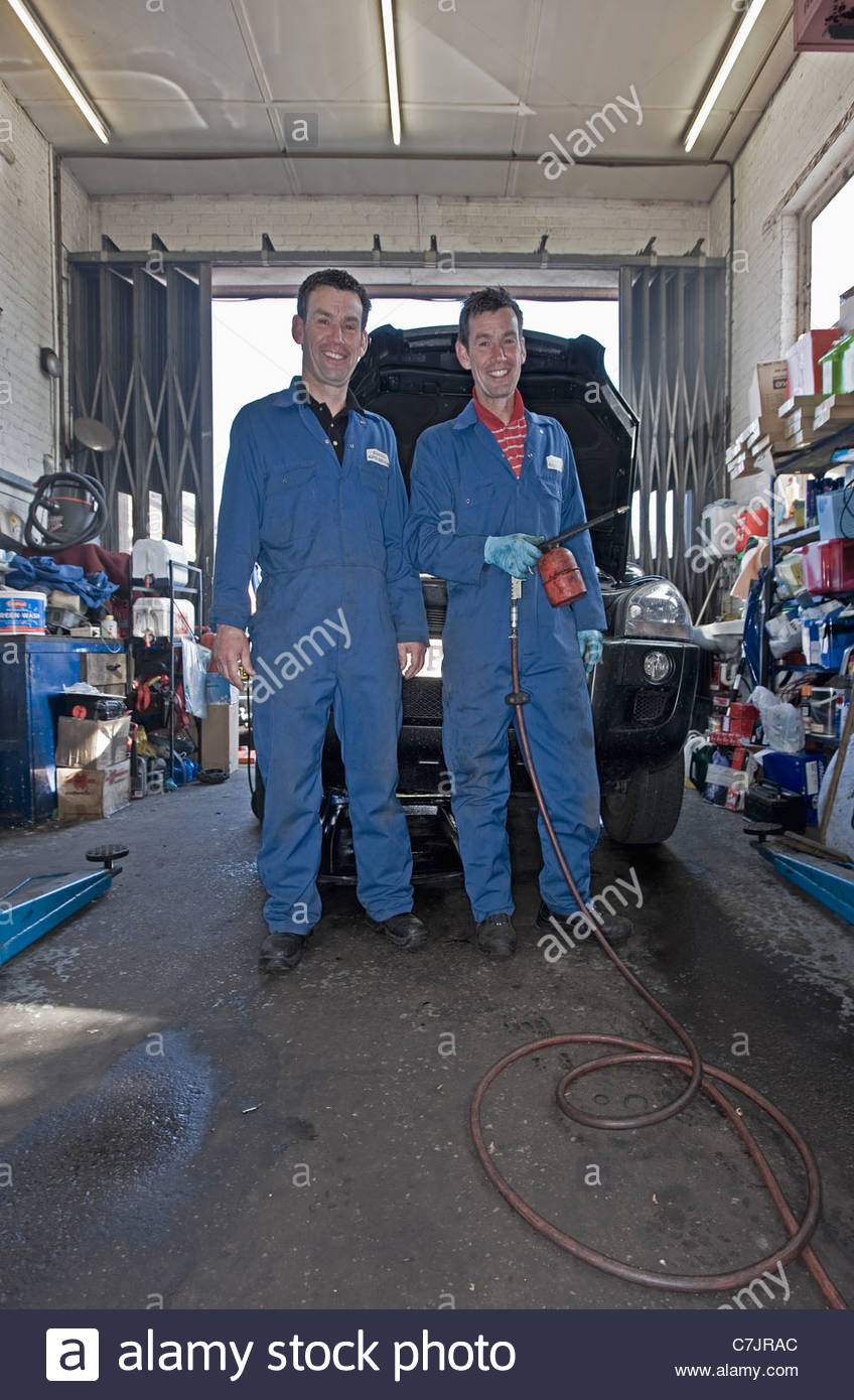 Mechanics smiling in auto repair shop - Stock Image