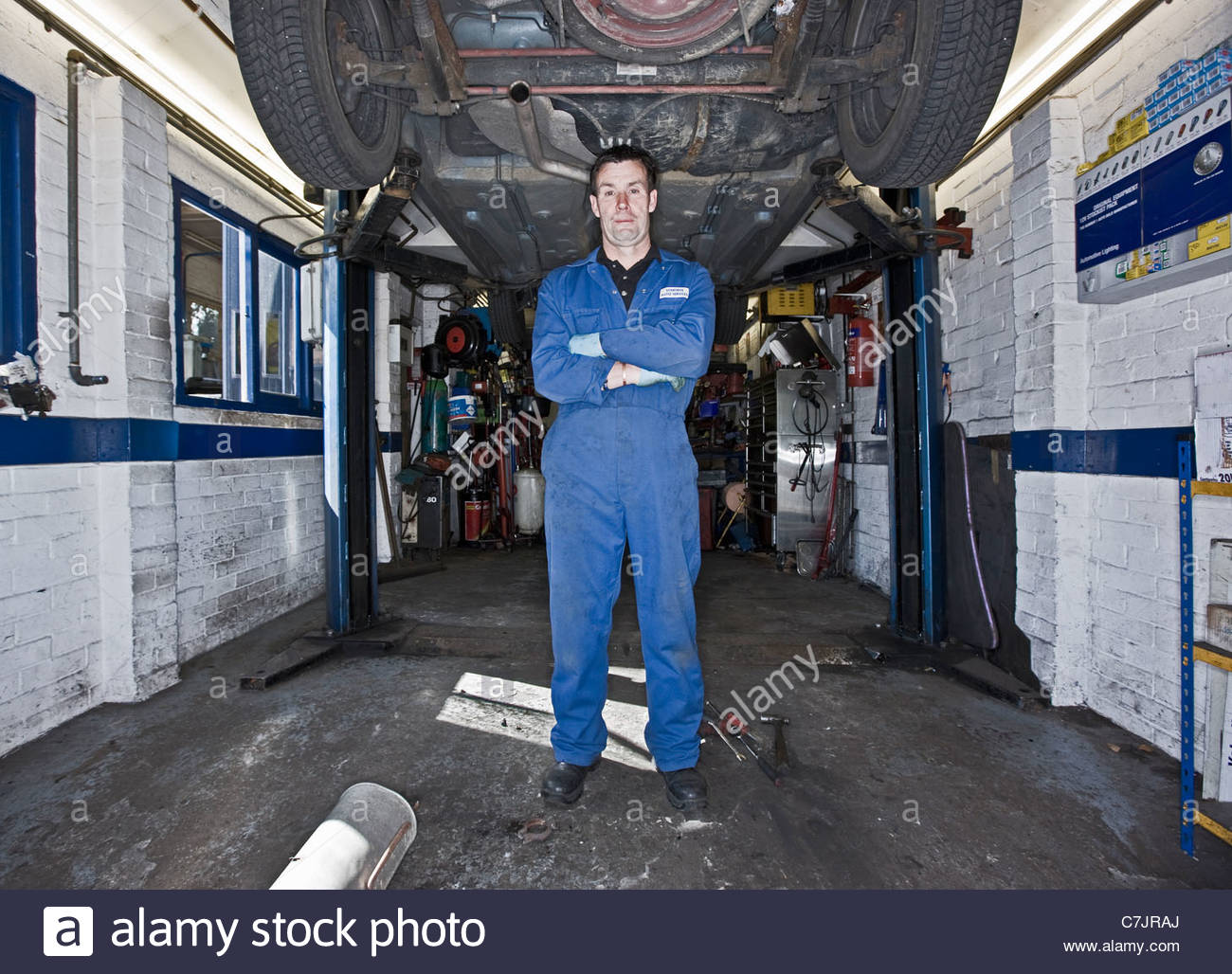 Mechanic standing under lifted car - Stock Image