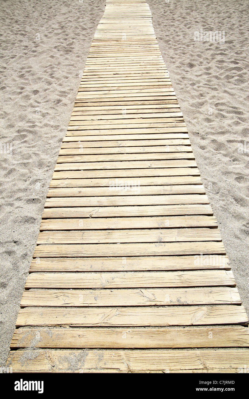 Perspective of wooden path at sandy beach - Stock Image