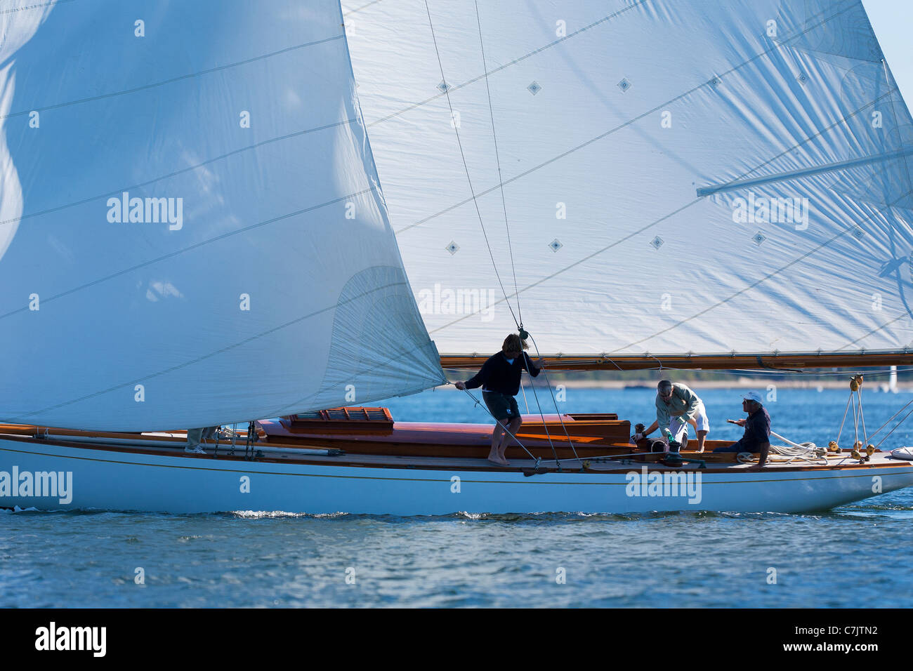 A crew pulls the tack of the headsail in after completing a tack on board the William Fife designed yacht Clio - Stock Image