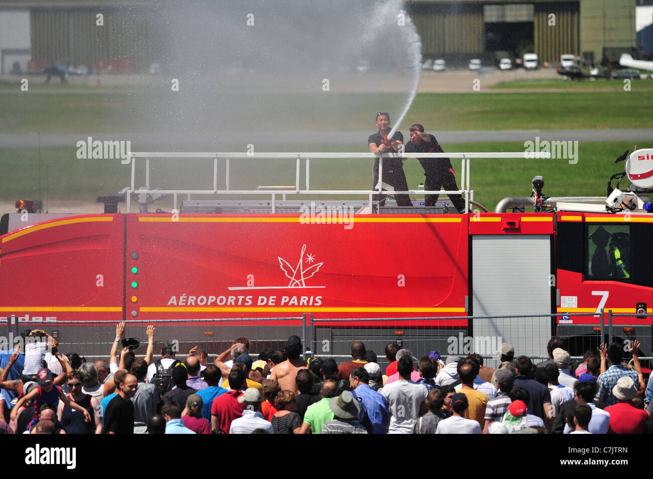 French Firefighters cooling crowd during  extremely hot weather, at Le Bourget airshow 2011 - Stock Image