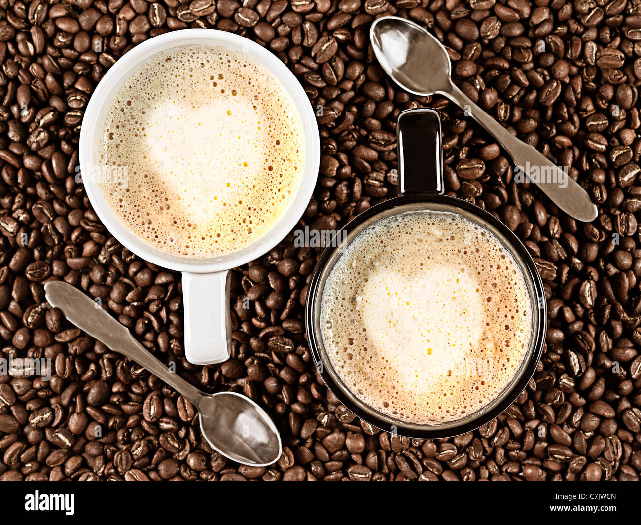 Two cups with Cafee Latte with heart shaped rosetta surrounded by coffee beans and spoons - Stock Image