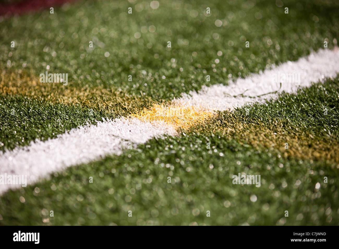 Astro Turf with white and yellow soccer lines - Stock Image
